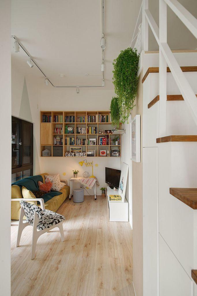 Стеллаж для книг на стене гостиной и небольшой рабочий столик под ним
