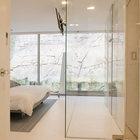 Душ в главной спальне отделен прозрачным стеклом. (спальня,дизайн спальни,интерьер спальни,минимализм,интерьер,дизайн интерьера,мебель)