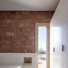Изголовьем кровати служит нижняя оштукатуренная часть стены, а вместо прикроватных полочек деревянные полочки.