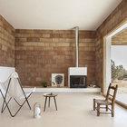 Минималистский интерьер гостиной с не оштукатуренными блоками и минимумом мебели. Керамические блоки, конечно не кирпич, но смотрятся тоже интересно. Дровяной камин способен согреть, когда на улице прохладно и добавляет романтики интерьеру.