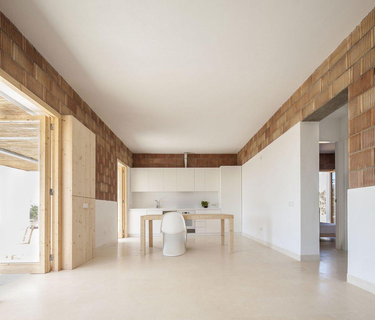 Белая минималистская кухня расположена в торце жилой комнаты и не доминирует в интерьере