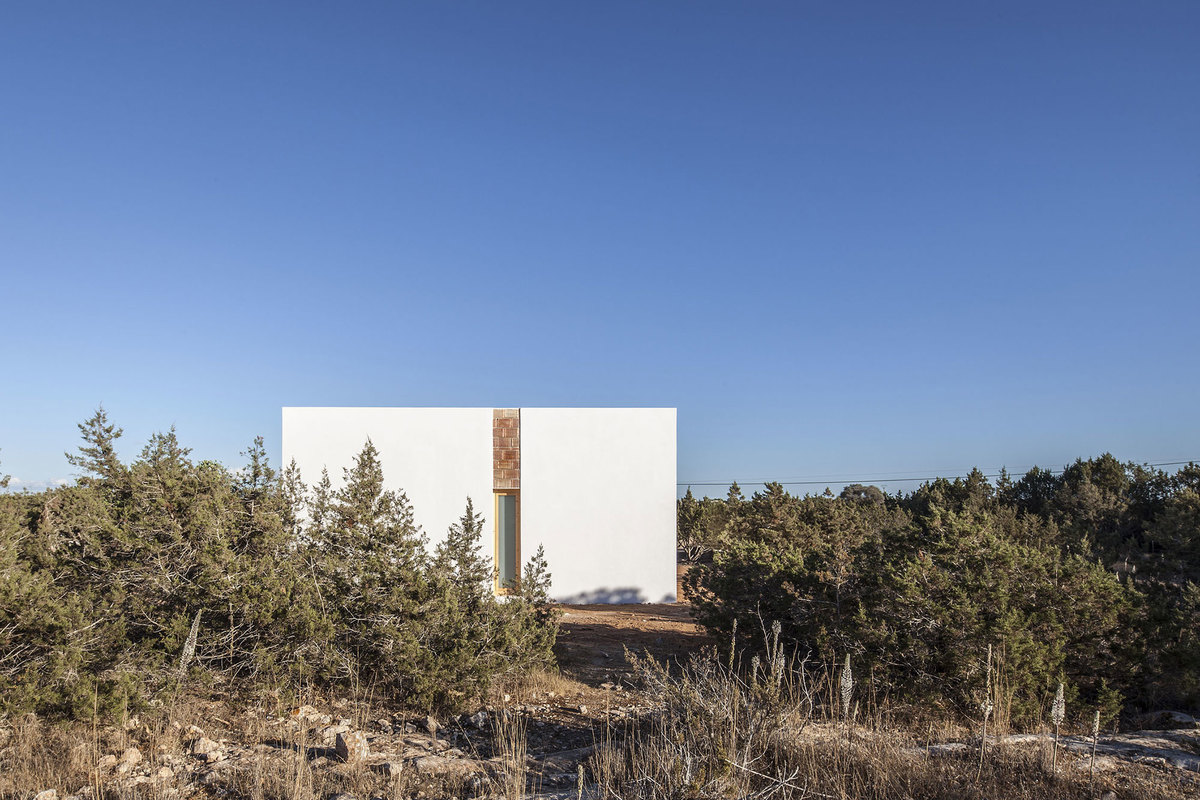 Белые фасады дома явно выделяются на фоне местных ландшафтов.
