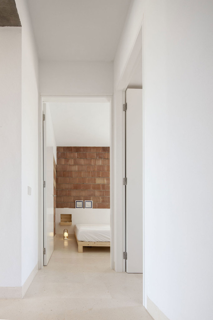 Интерьер спальни построен на натуральных текстурах дерева и терракоты керамических блоков на нейтральном белом фоне.
