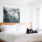 Деревянная кровать занимает почти всю небольшую спальню-лофт. Большое окно занимает почти все окно.