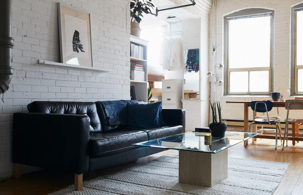 Кожаный диван на фоне кирпичной стены смотрится украшением гостиной.