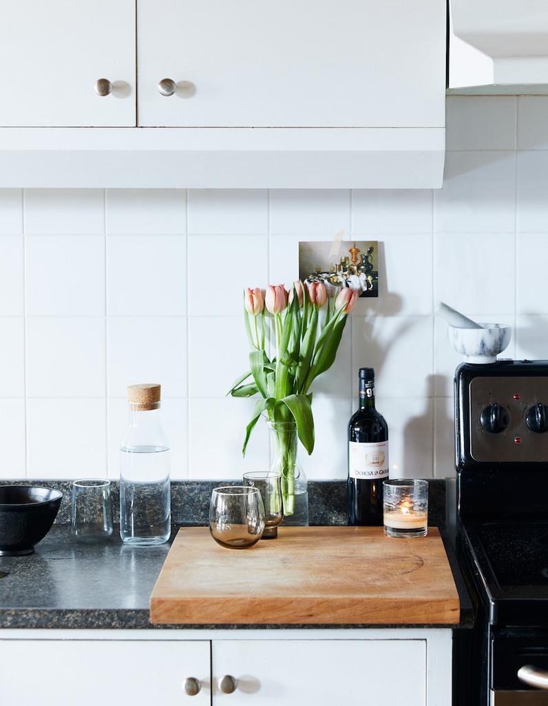 Кухонная столешница может восприниматься как еще одна поверхность в гостиной и цветы на ней смотрятся весьма уместно