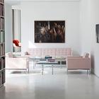 Гостиная переходящая в библиотеку на первом этаже нового здания. Розовые кресла и стеклянные столики немного разнообразят минималистское пространство гостиной с белыми стенами и светло-серым бетонным полом