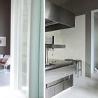 Промышленная кухня с массивной вытяжкой из нержавейки удивительным образом сочетается с минималистским дизайном стульев Тюлип Ээро Сааринена.