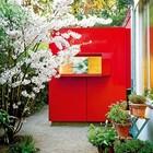 Ярко-красная пристройка ванной к дому выделяется на фоне основного здания.