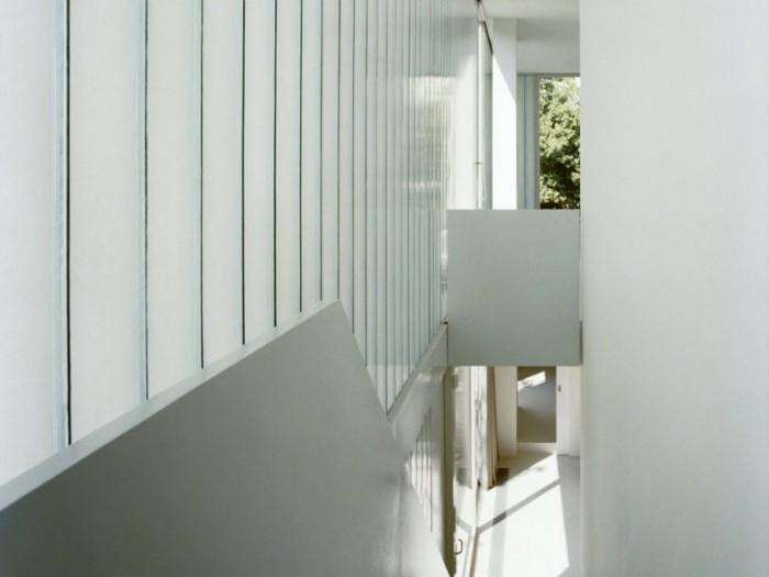 Лестница ведущая на второй этаж хорошо освещена благодаря стенам из стеклопрофилита.