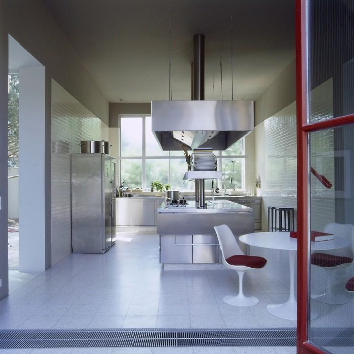 С открытыми остекленными воротами кухня столовая становится комнатой на открытом воздухе.