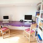 Рабочее место для двоих школьников с сиреневой столешницей, книжными полками во всю стену и потолочным освещением над рабочим столом.