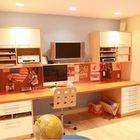 Современное рабочее место с большим столом и оргтехникой рядом с кухней.