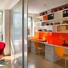 Современный яркий домашний офис с красной столешницей и оранжевыми стульями.