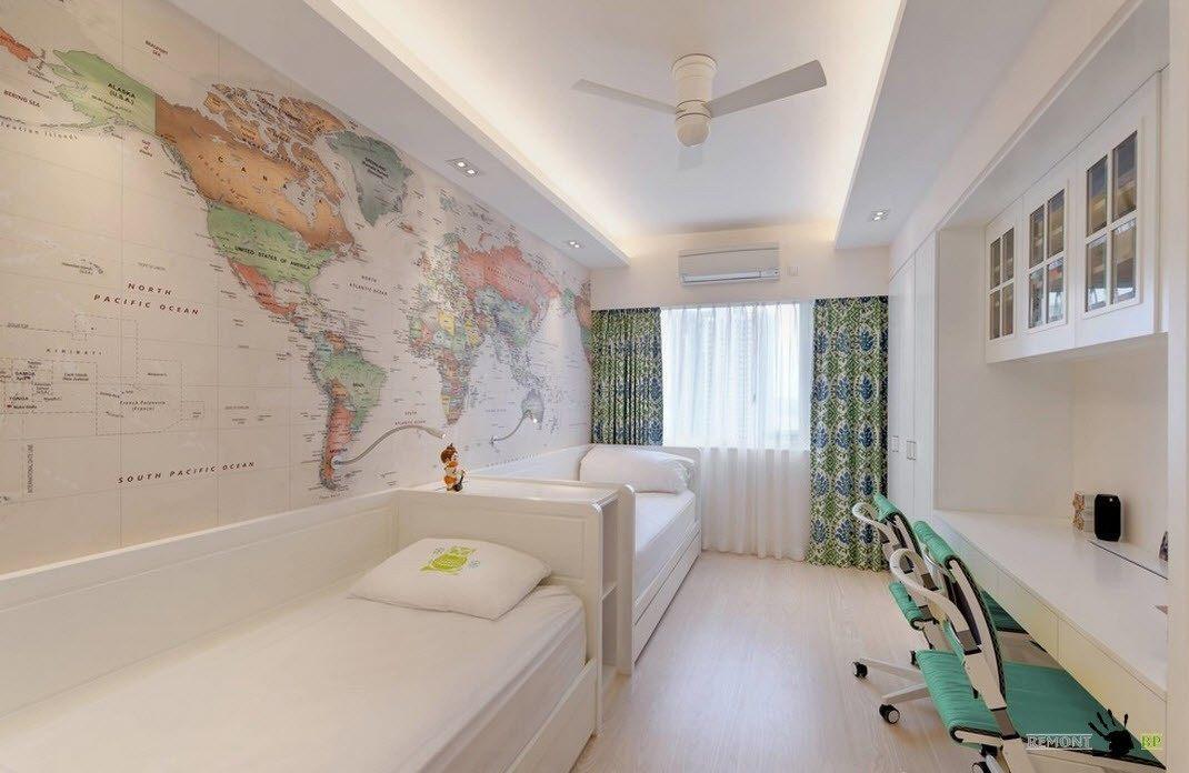 Политическая карта мира на стене белой минималистской детской для двух школьников. Длинный рабочий стол позволяет одновременно учиться двоим детям.