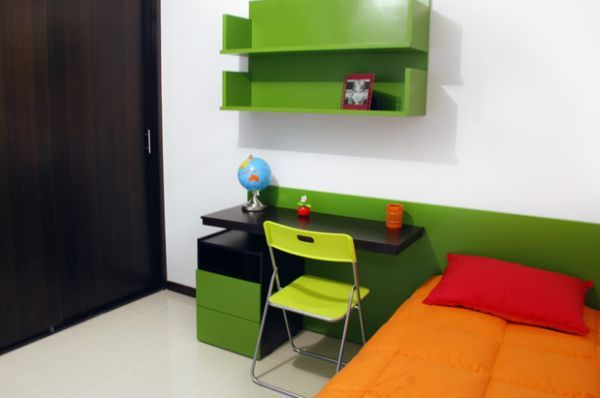 Современная детская с рабочим столом рядом с кроватью. Спальню оживляют зеленые и оранжевые акценты.