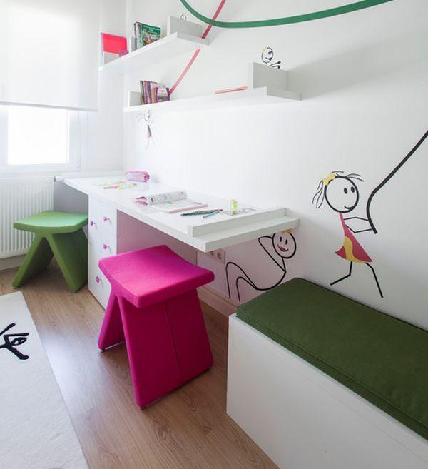 Т-образный рабочий стол для двух школьников с необычными цветными табуретами. Атмосферу в комнате создают забавные человечки на стене.
