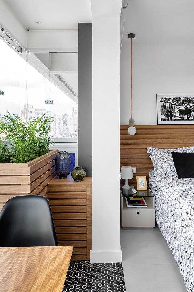 Пространство организовано таким образом, что на балкон можно попасть как из спальни, так и из кухни. Деревянные ящики в углу балкона закрывают кондиционер и служат цветочными вазонами