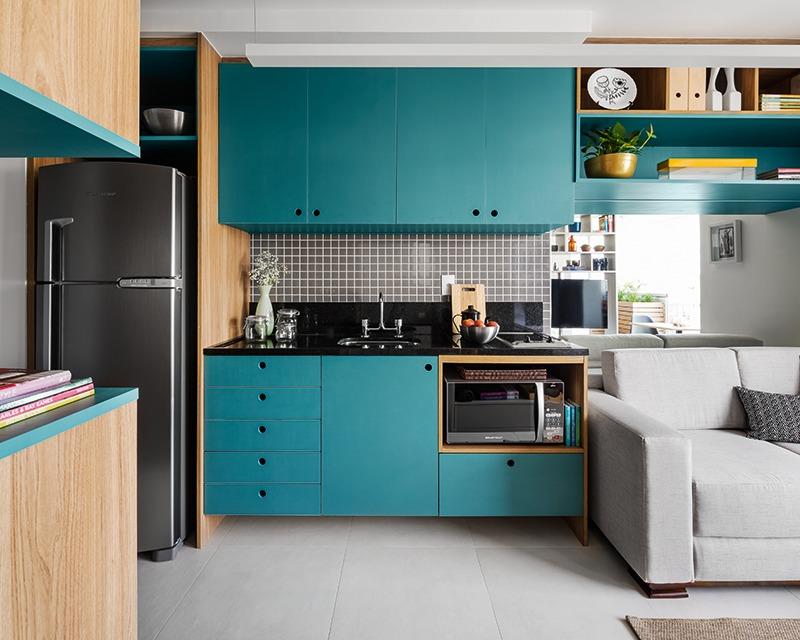 Темно-бирюзовый цвет кухонного фасада, по задумке дизайнера, визуально расширяет небольшое жилое пространство квартиры.