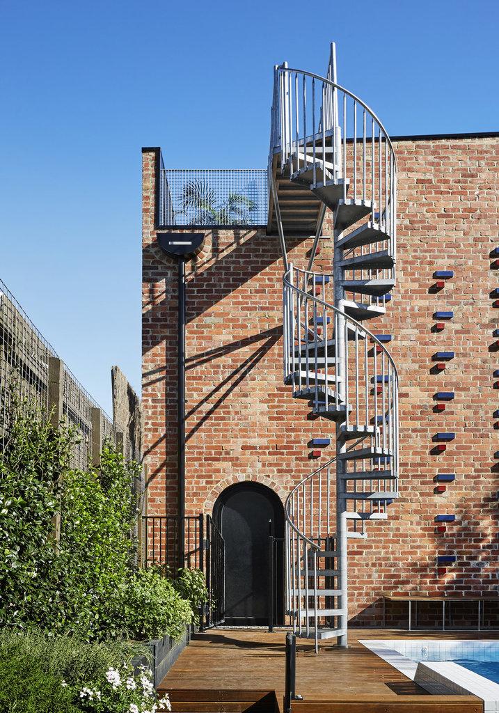 Ажурная стальная лестница ведущая на террасу  на крыше дома несколько отстоит от дома, чтобы занимать на земле как можно меньше места