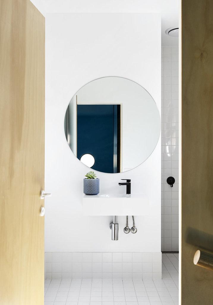 Белая и светлая ванна с простым белым кафелем на полу и в душе. Круглое зеркало повторяет формой окна дома