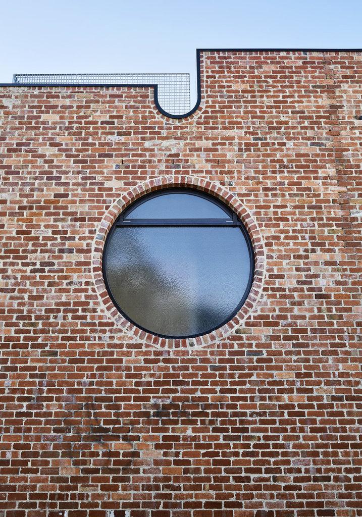 Большое круглое окно на фасаде выполнено из матового стекла дабы не нарушать приватности жильцов дома