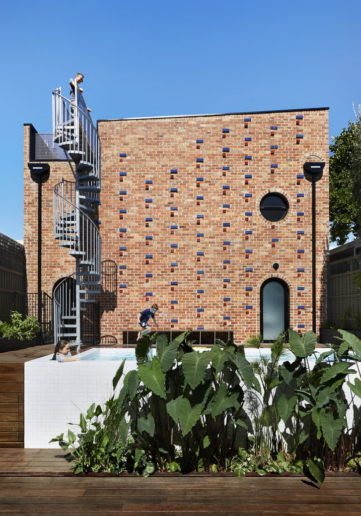 Хорошо видны красные и синие кирпичи украшающие фасад дома, а также остекленные скругленные двери ведущие в дом