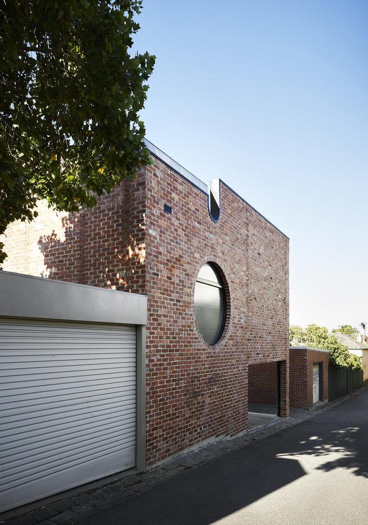 Круглые окна и фигурные парапеты украшают здание из красного кирпича.