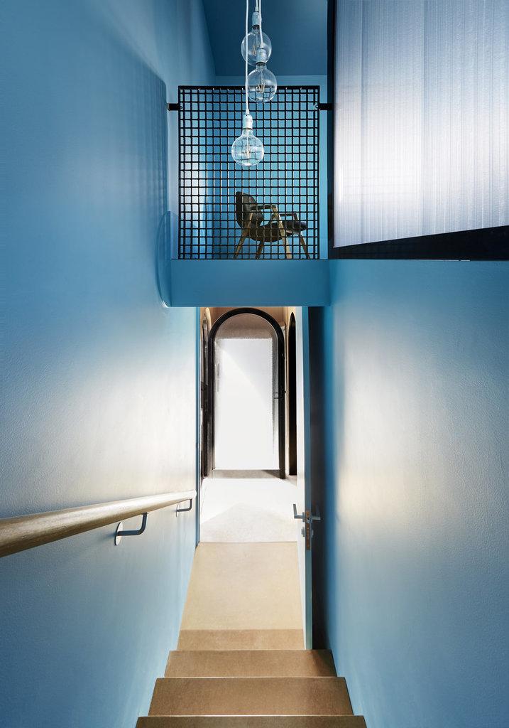 Лестница со двора ведет в гостиную на втором этаже. Скругленные стеклянные двери дополняют круглые окна