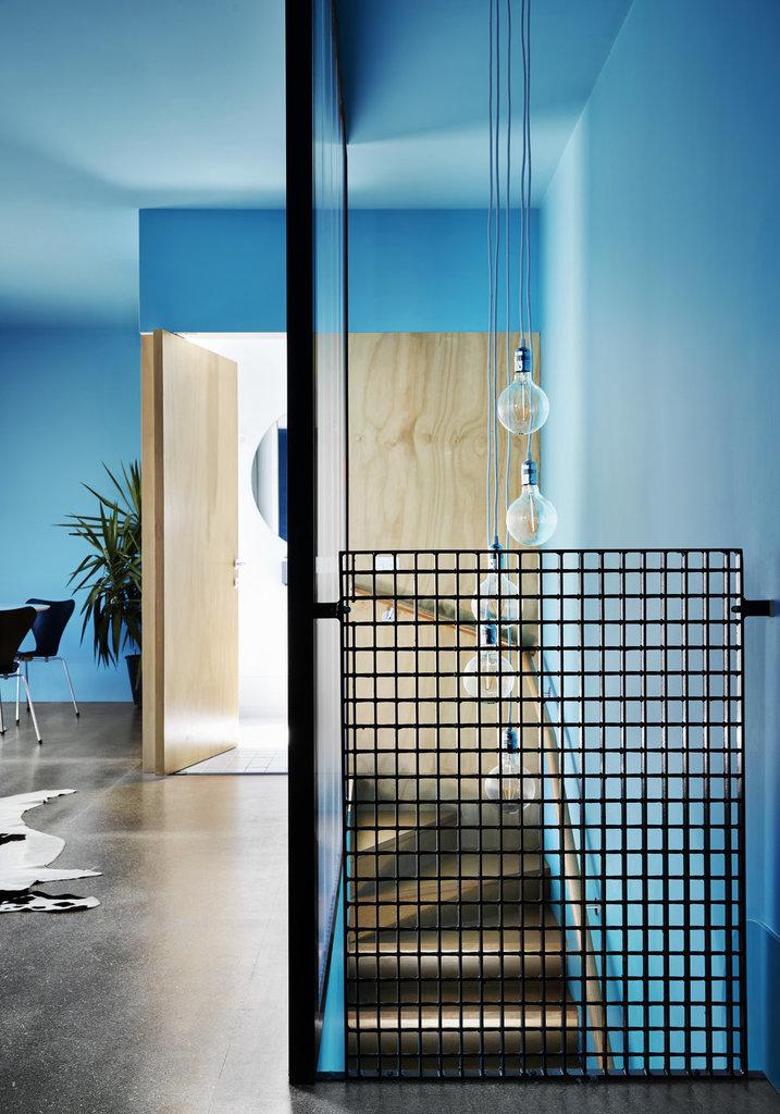От гостиной лестница скрыта матовой перегородкой, которая в то же время рассеивает свет ламп над лестницей