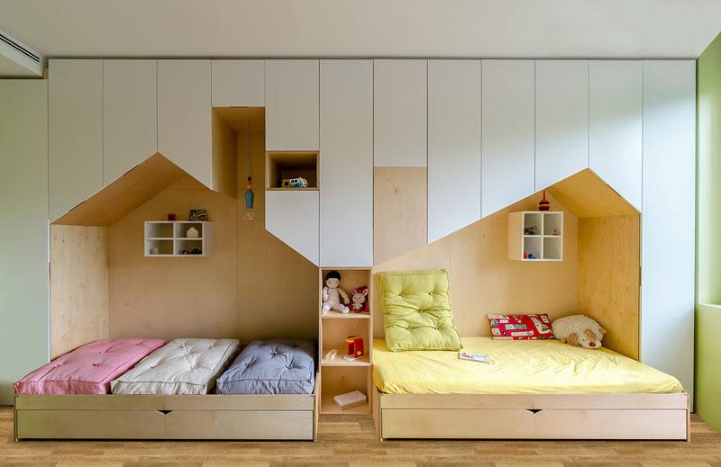 Одну из стен детской полностью занимают белые шкафы с нишами в виде домиков или коттеджей.