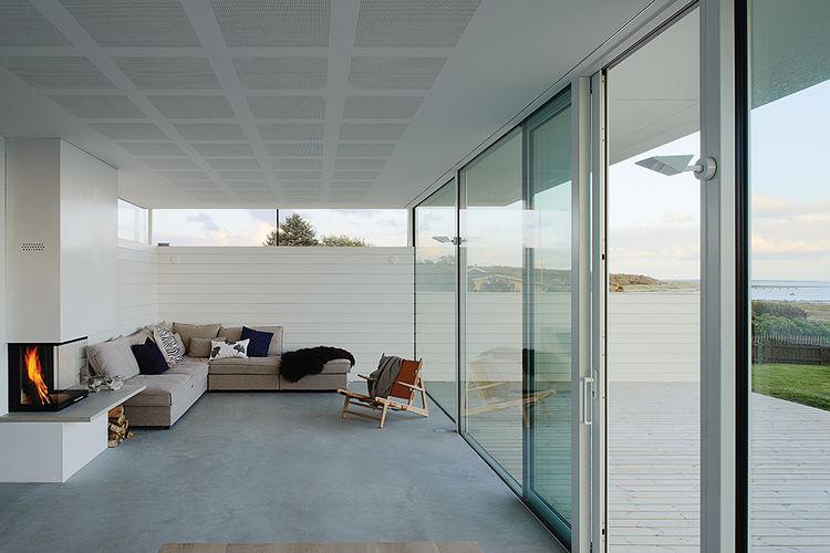 Гостиная благодаря остекленной стене максимально использует роскошный вид на море открывающийся с места расположения дома.