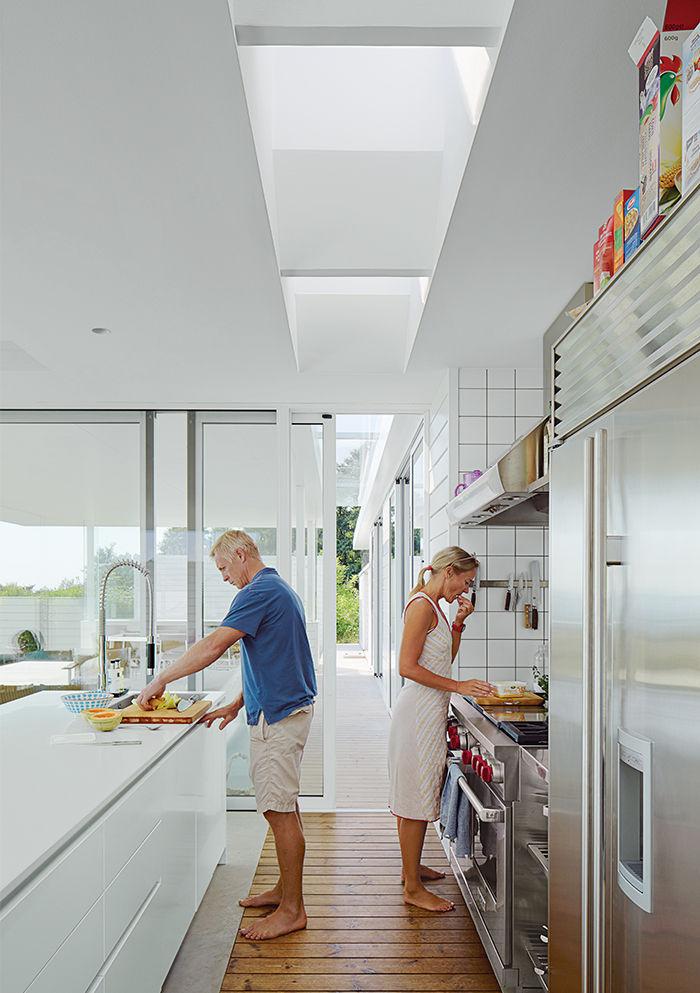 Из кухни сдвижная стеклянная дверь ведет на террасу в жилую комнату на открытом воздухе.