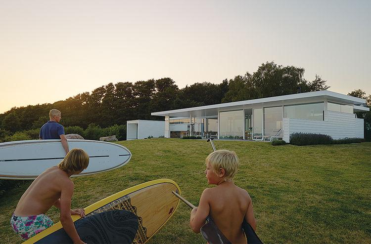 Простой модернистский фасад одноэтажного пляжного дома.