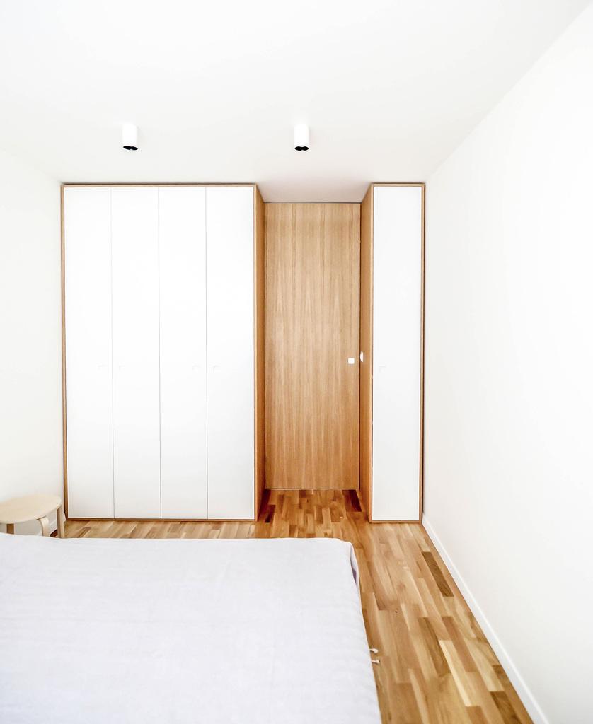 Интерьер минималистской спальни построен на контрасте холодного белого и теплой древесной текстуры.