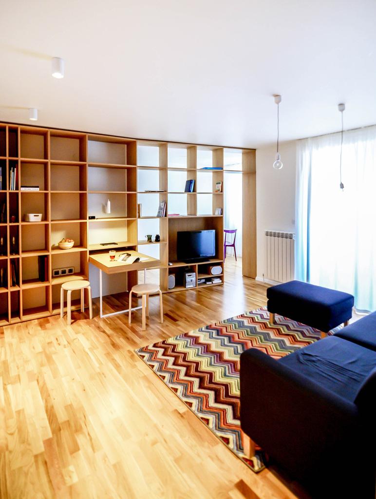 Кабинет хозяйки квартиры отделен от жилой комнаты двусторонним деревянным стеллажом