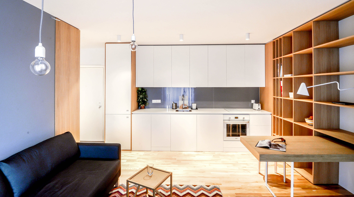 Когда кухня является частью жилой комнаты, есть два варианта - сделать ее центром жизни, либо практически спрятать ее сделав максимально нейтральной и малозаметной