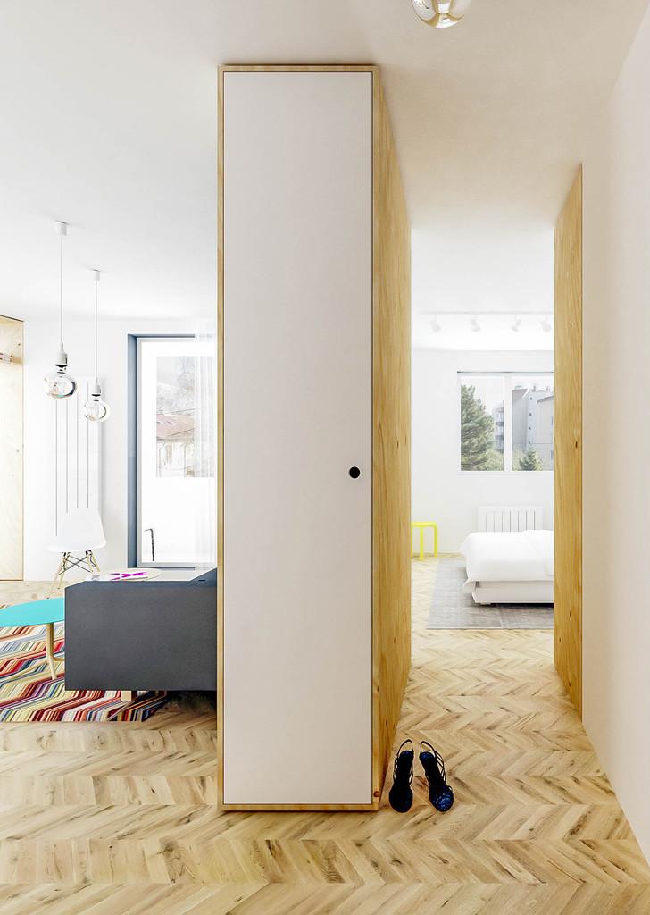 Узкий коридорчик ведет в спальню. Между комнатами отсутствует порог, а пол по всей квартире покрыт светлым паркетом
