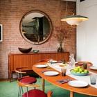 Обеденный стол в гостиной рядом с кухней. Круглое зеркало на кирпичной стене украшает интерьер гостиной. (индустриальный,лофт,винтаж,стиль лофт,индустриальный стиль,современный,интерьер,дизайн интерьера,мебель,архитектура,дизайн,экстерьер,квартиры,апартаменты,1950-70е,середина 20-го века,медисенчери,медисенчери модерн,модерн,средневекоый модерн,модернизм,mcm,столовая,дизайн столовой,интерьер столовой,мебель для столовой,фото столовой,идеи столовой)