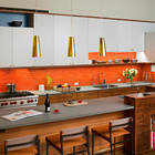 Яркий оранжевый кафель кухонного фартука делает интерьер ярче и жизнерадостней. Кухонный остров традиционно служит барной стойкой.
