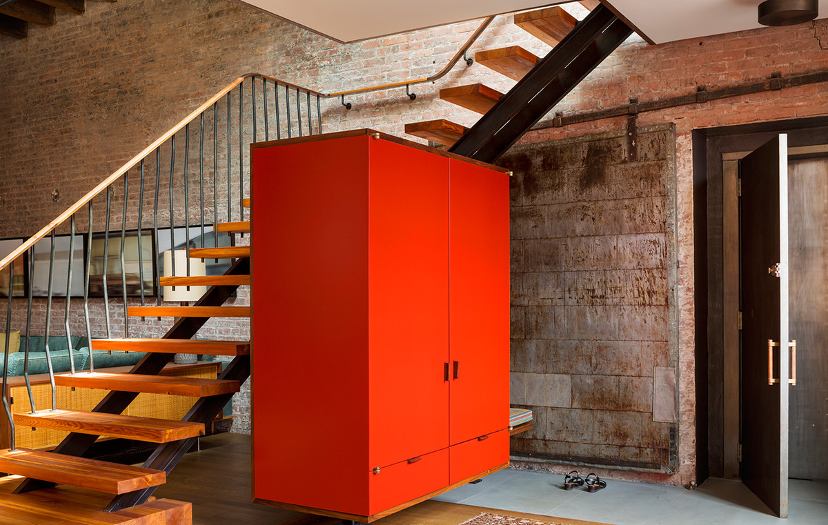 Красный шкаф парящий в воздухе в прихожей. Лестница за шкафом ведет на второй этаж квартиры.