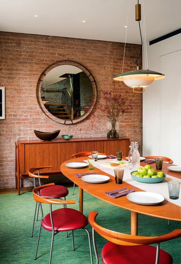 Обеденный стол в гостиной рядом с кухней. Круглое зеркало на кирпичной стене украшает интерьер гостиной.