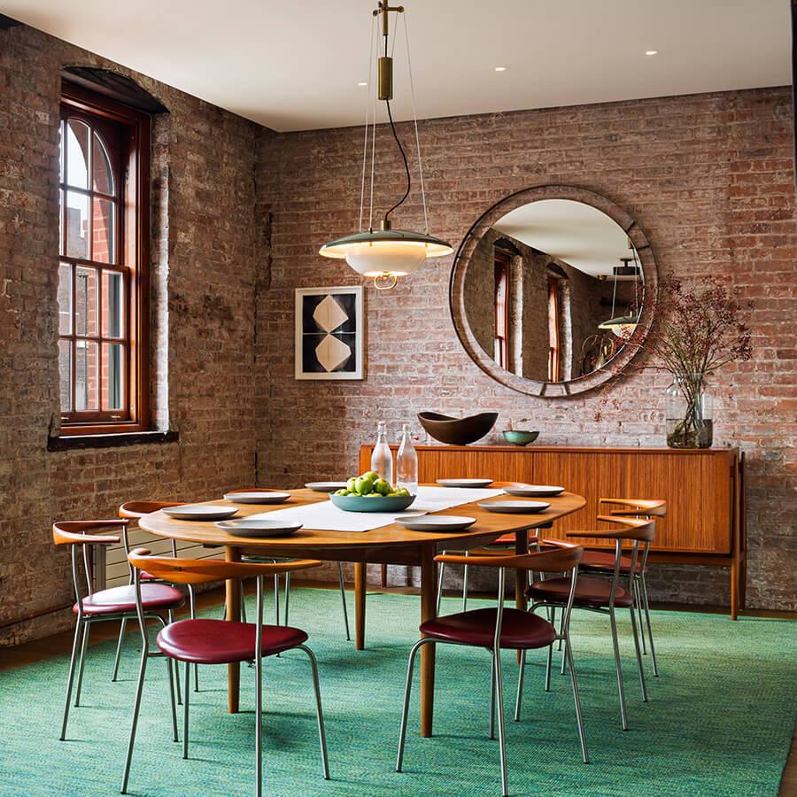 В столовой кирпичная кладка стен отлично сочетается с модернистской мебелью середины прошлого века.