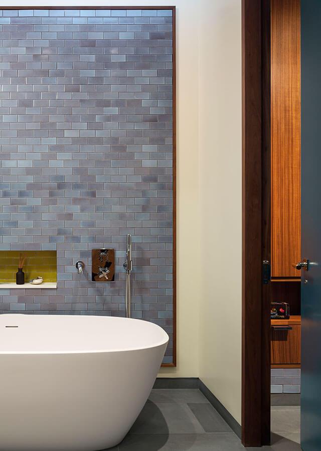 В ванной комнате рядом с главной спальней уникальным образом использована кафельная плитка. Кафельная плитка на стене рядом с отдельно стоящей ванной выложена ковром и обрамлена в деревянную рамку.