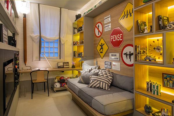 Рабочий стол ребенка расположен у окна, а кровать встроена прямо в стеллажи занимающие всю длинную стену комнаты.