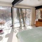 Спальня на втором этаже расположена за кухней. Эта спальня имеет большую площадь остекления чем нижняя спальня. Через остекленные стены открывается впечатляющий вид на прилегающий лес.