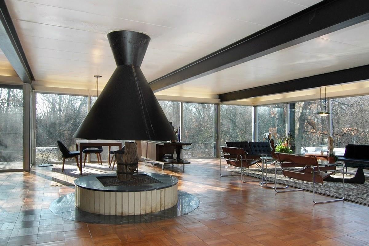 Холодные стальные балки на потолке противопоставляются теплому деревянному паркету и камину, также несущему тепло и уют в интерьер комнаты. На потолке вдоль окон можно заметить мягкую подсветку