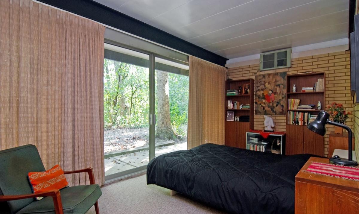 Спальня на первом этаже с полностью остекленной стеной и выходом в сад.