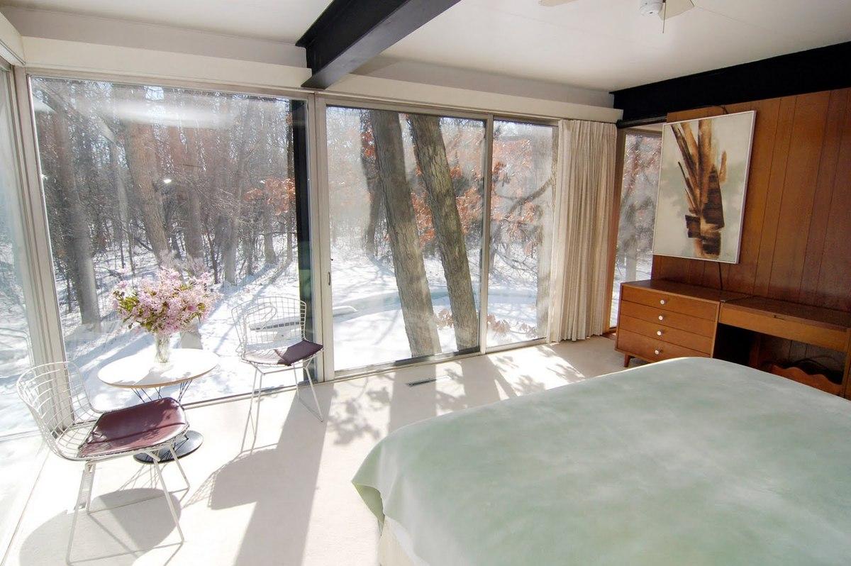 Спальня на втором этаже расположена за кухней. Эта спальня имеет большую площадь остекления чем нижняя спальня. Через остекленные стены открывается впечатляющий вид на прилегающий лес