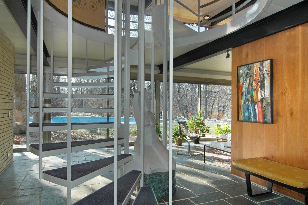 Светлый остекленный холл первого этажа со стальной винтовой лестницей ведущий в жилую комнату на втором этаже.